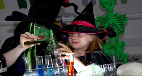 A woman and girl dressed as witches make potions.