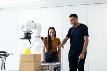 The image selected as the TechEthos website homepage banner shows two innovators discuss a robotic arm.
