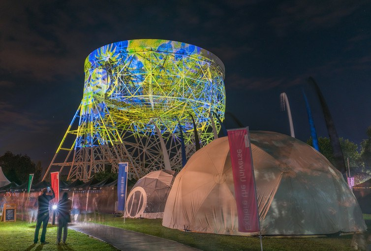 The Lovell radio telescope of Jodrell bank lit up during the Bluedot festival by the Brian Eno art installation project.
