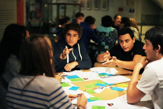 A group of students pictured around a table while playing a PlayDecide game
