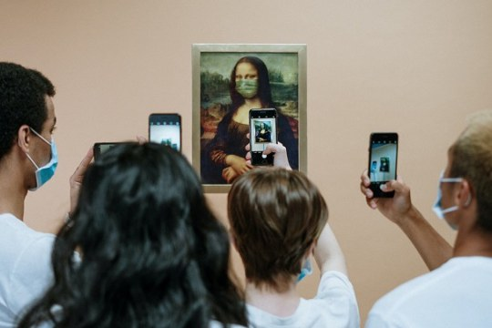 People taking a picture of the Mona Lisa wearing a face mask.